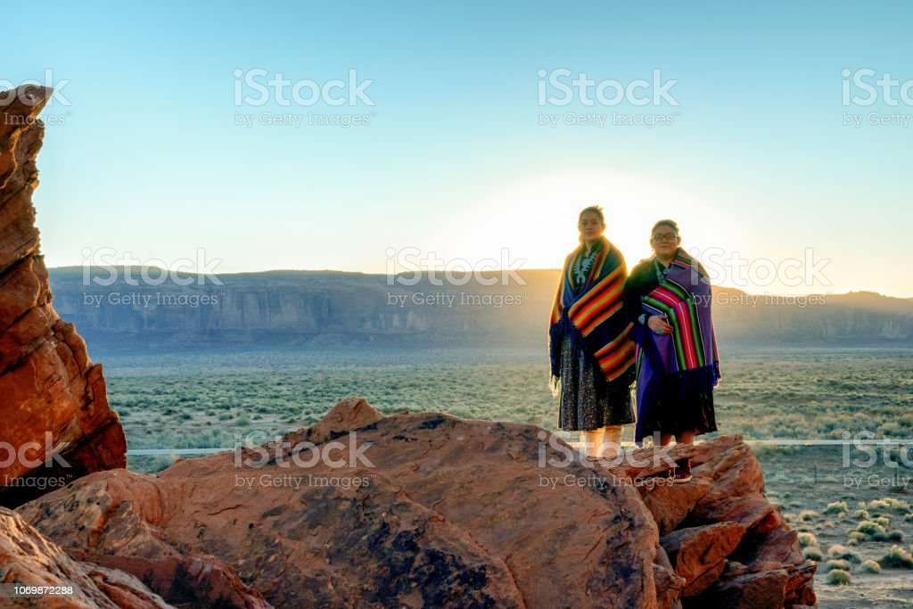 Two Traditional Navajo Native American Sisters In Monument Valley Tribal Park on a Rocky Butte Enjoying a Sunrise or Sunset Pretty Navajo girls wrapped in handwoven traditional blankets enjoying a grand sunrise or sunset in Monument Valley Arizona Stock Photo