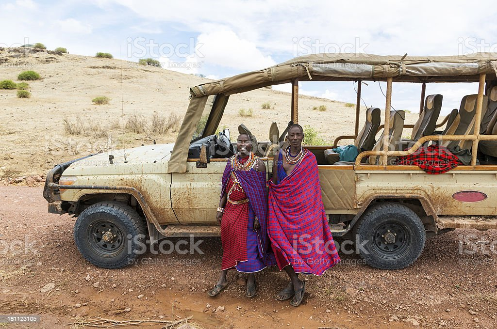 Two traditionally dressed maasai in front of safari jeep stock photo