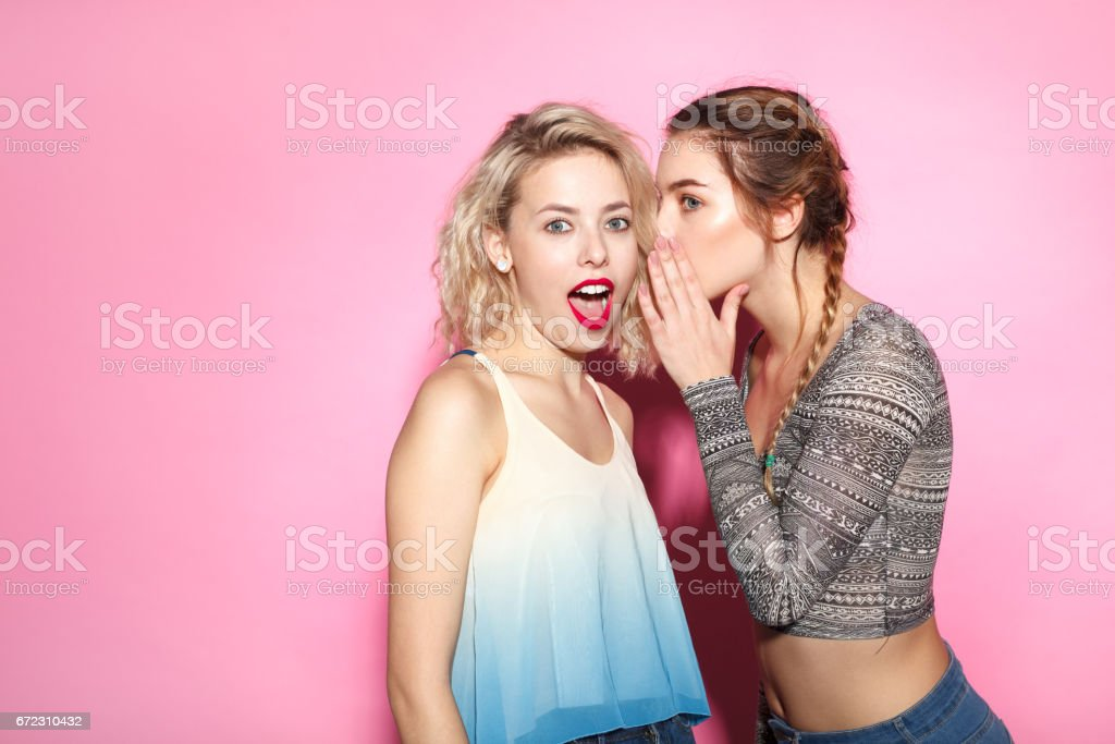 Two trendy girl exchanging news stock photo