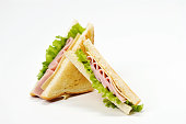 Two triangular sandwiches with cheese and ham. The sandwich is made from slices of fried white bread. Close-up. White background.