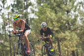 Two cyclists race during the bicycling stage of a triathlon. They are on a highway out in a rural area surrounded by grass and pine trees. The woman is in front.