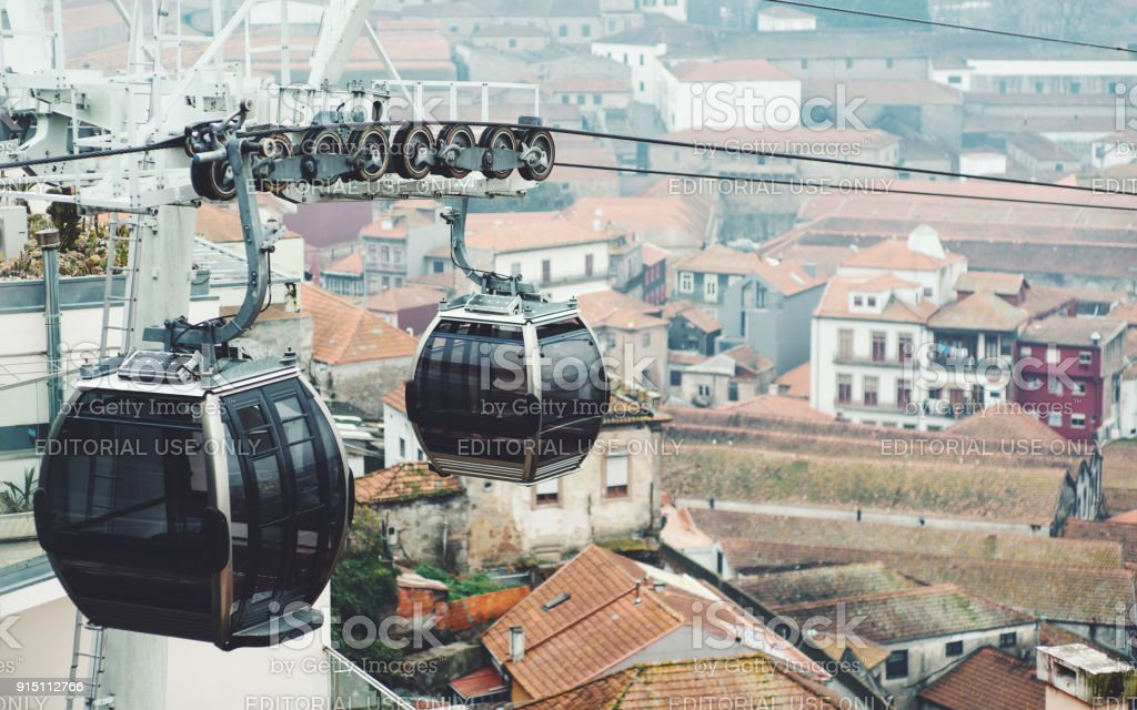 Two trolleys of ropeway with cityscape behind stock photo
