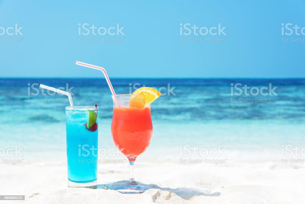 Two tropical drinks on white sandy beach stock photo