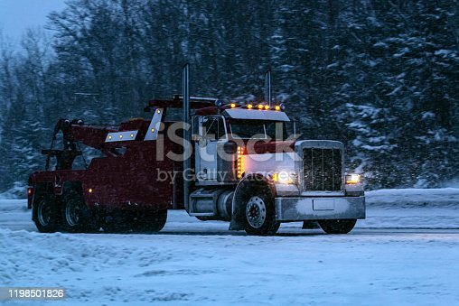 A heavy tow truck travels a snow covered highway.