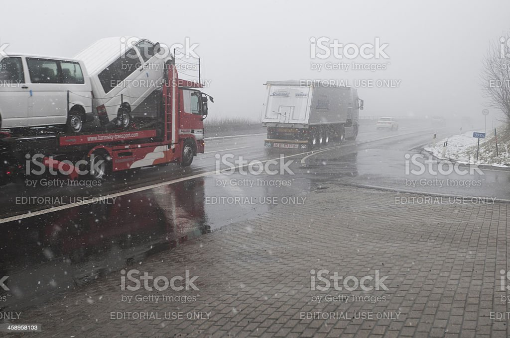 Two trucks driving in dense fog and snow royalty-free stock photo
