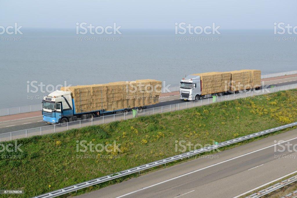 Twee vrachtwagens geladen met Balen stro foto