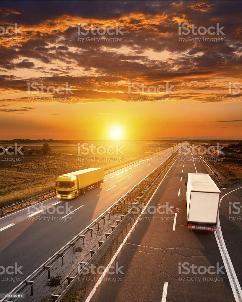 Dos camiones en la carretera al atardecer - foto de stock