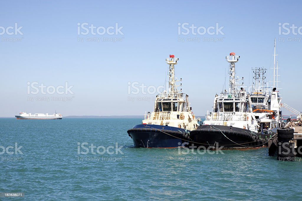 Two tug boats at jetty with blue sky and sea royalty-free stock photo