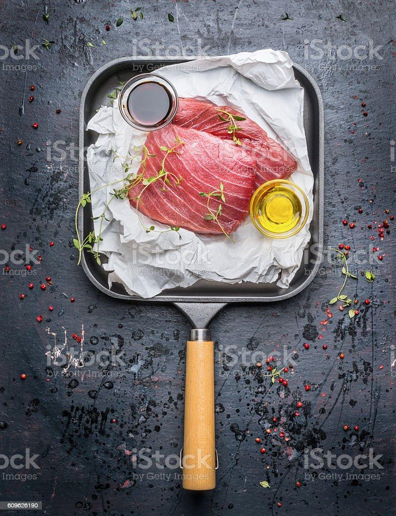 Two tuna steaks ,oil and fresh seasoning in frying pan - foto de acervo