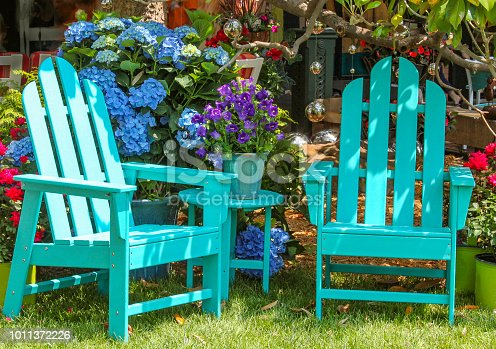 Two turquoise Adirondack chairs and a matching table surrounded by beautiful flowers and trees and shining mirror balls handing from the branches above