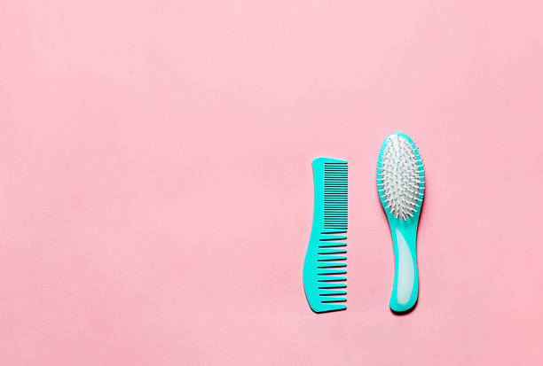 Two Turquoise hair comb crest brushes with handle for all Two Turquoise hair comb crest brushes with handle for all hair types, isolated on pink copy space background. Feminine flat lay hairbrush stock pictures, royalty-free photos & images