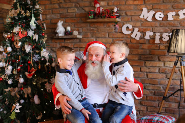 Two twin boys alternately make wish in ear of Santa Claus in de Lovely boys of same appearance sit on lap Santa Claus who sits large and soft armchair whisper in ear cherished wishes for New Year cozy spacious room decorated Years holidays with floor lamp, walls which hang Christmas posters, And high bright tree, under lie gifts boxes tied ribbons. Beautiful young male children European dressed warm sweaters blue jeans socks, gray long beard red suit white trim pointed cap pompon end. Concept traditions family happy Year, laughter carefree childhood friendly twin brothers, interior decorations, desired tree positive emotions eve holidays, active pastime children foolishness, holiday attributes symbols, desire magic alternately stock pictures, royalty-free photos & images