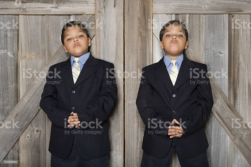 Two twin boys wearing suits stock photo