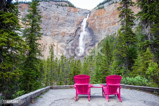 1131408581istockphoto two twin pink wooden chairs  facing a tall mountain waterfall 1162836971