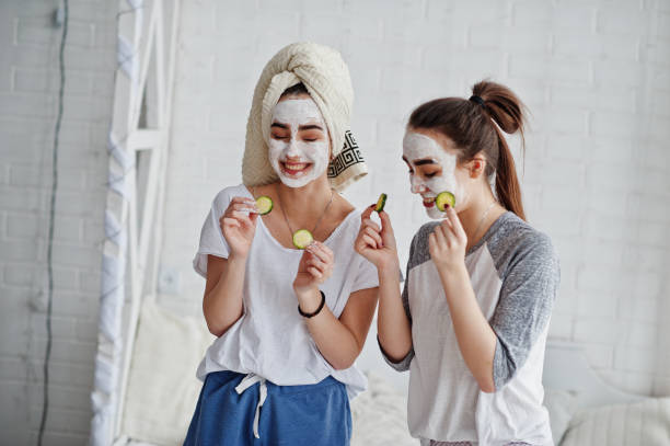 Two twins girls in pajamas with facial mask and cucumber slices. stock photo