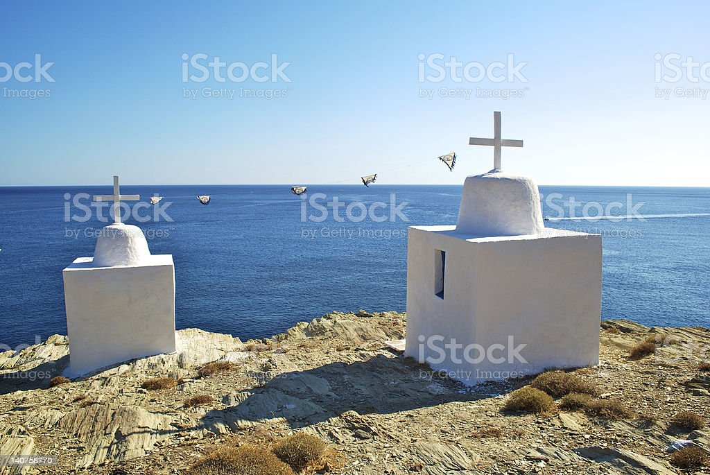 Two typical greek chapels on a rock near the sea, stock photo