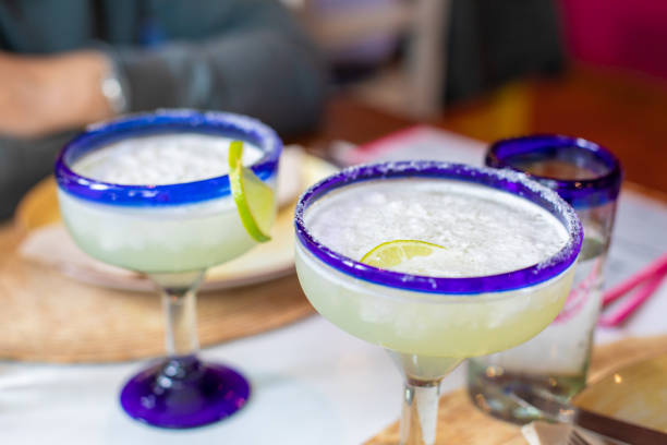 two typical mexican cups with margarita drink two crystal glasses full of cocktail drink margarita with slice lemon in typical mexican glass cups with blue edged line margarita stock pictures, royalty-free photos & images