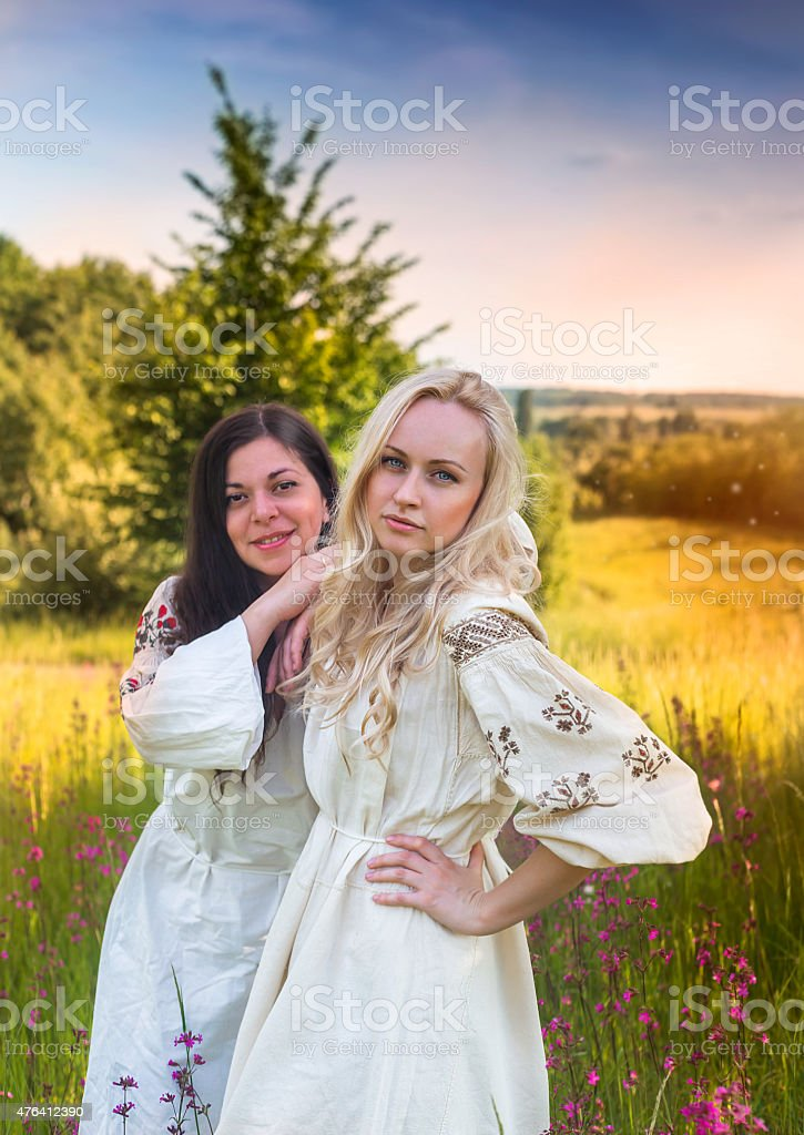 Two ukrainian girls in national costumes at the meadow stock photo