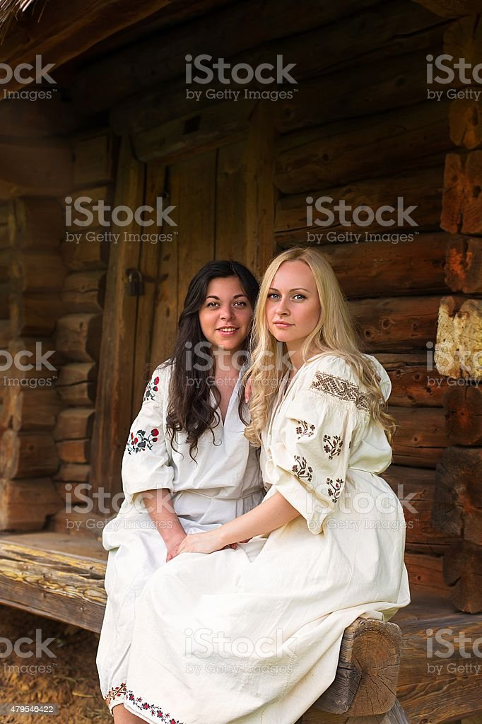 Two ukrainian girls in national costumes at the porch stock photo