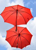 Two red umbrellas flying in the wind, with cloudy sky in the background.