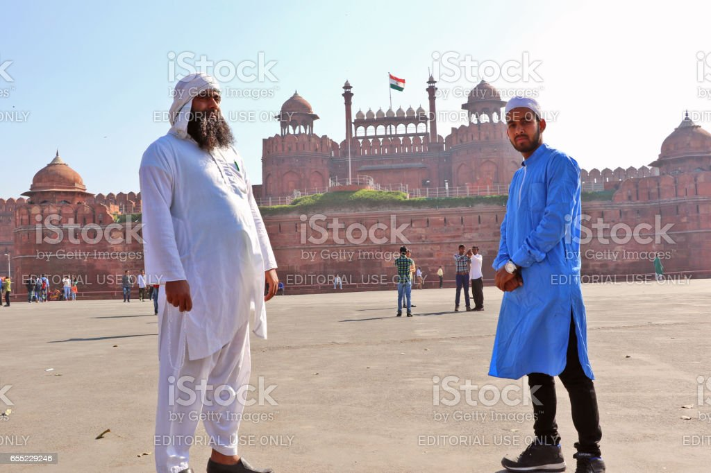 New Delhi, India - February 24, 2017: Two unidentified visitors saluting the Red Fort, Delhi, India a reminder of the magnificent power of the Mughal emperors and a symbol of glory to the Indian nation too. stock photo