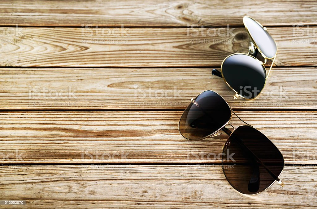 two unisex sunglasses on a wooden background top view stock photo