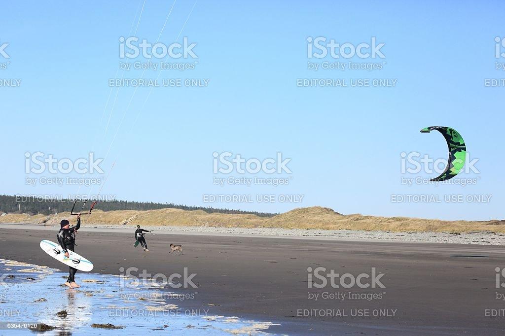 Two unknown men  with kitesurfing gear at Mavillette beach stock photo