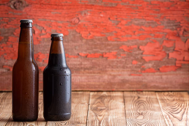 Two unlabelled beer bottles of different shapes stock photo