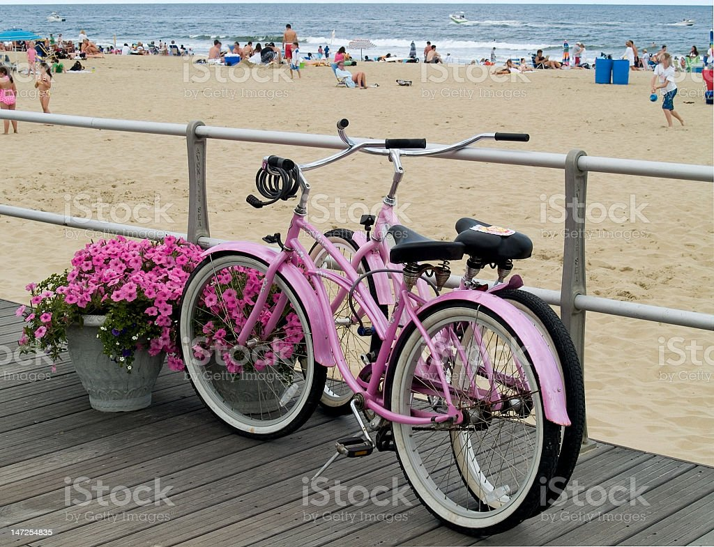 Two unlocked pick beach cruisers at the beach stock photo