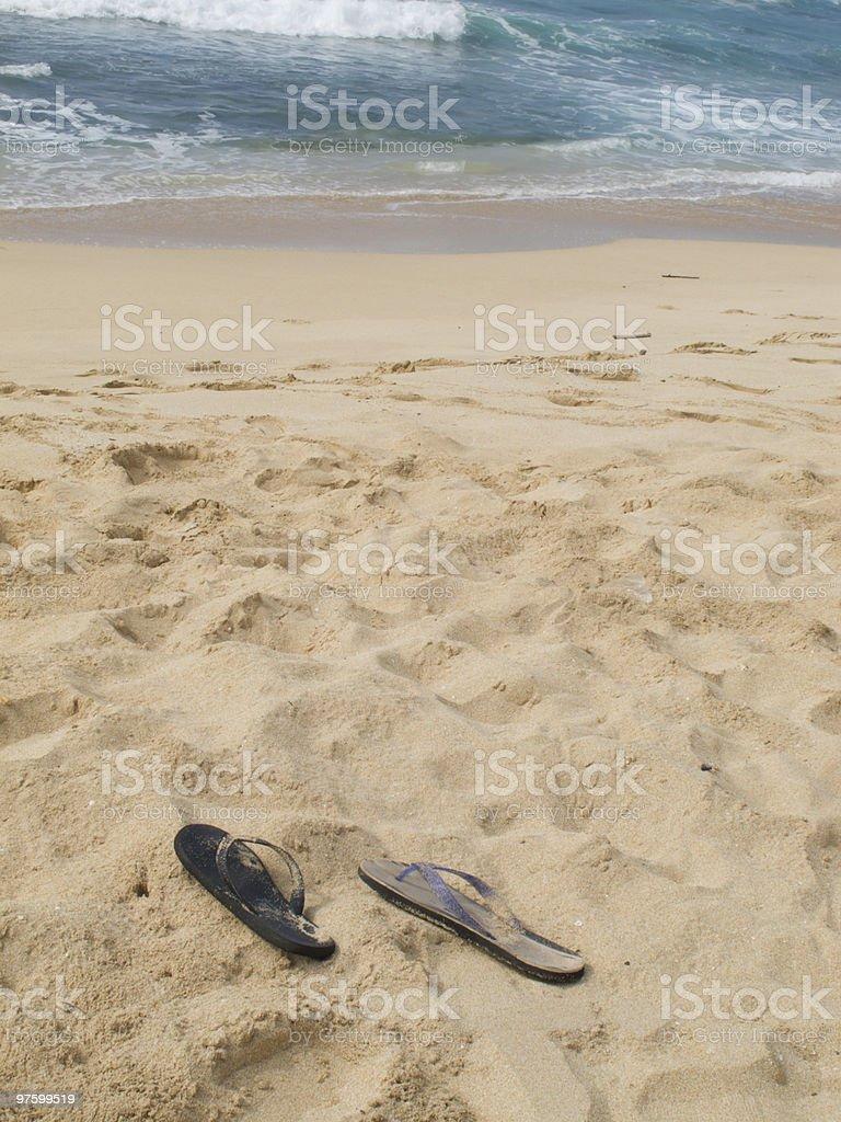 Two unmatching sandals among many footprints on sandy beach royaltyfri bildbanksbilder