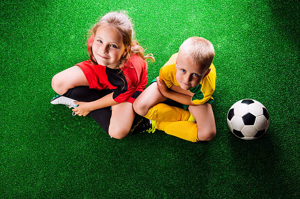Two unrecognizable little football players against green grass stock photo