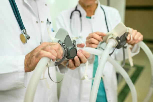 Zwei nicht wiederzuerkennende medizinische Sanitätskräfte mit zwei Atemmasken – Foto