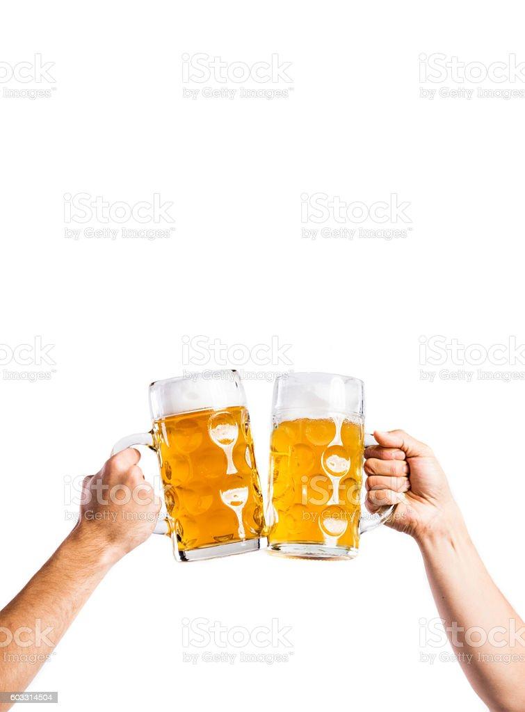 Two unrecognizable men clinking with beer mugs, studio shot - foto de stock
