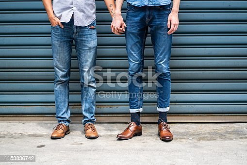 Unrecognizable male same-sex partners standing outside and holding hands on day, only human limbs