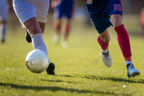 two unrecognizable soccer players running with a ball on a match. - soccer competition stock photos and pictures