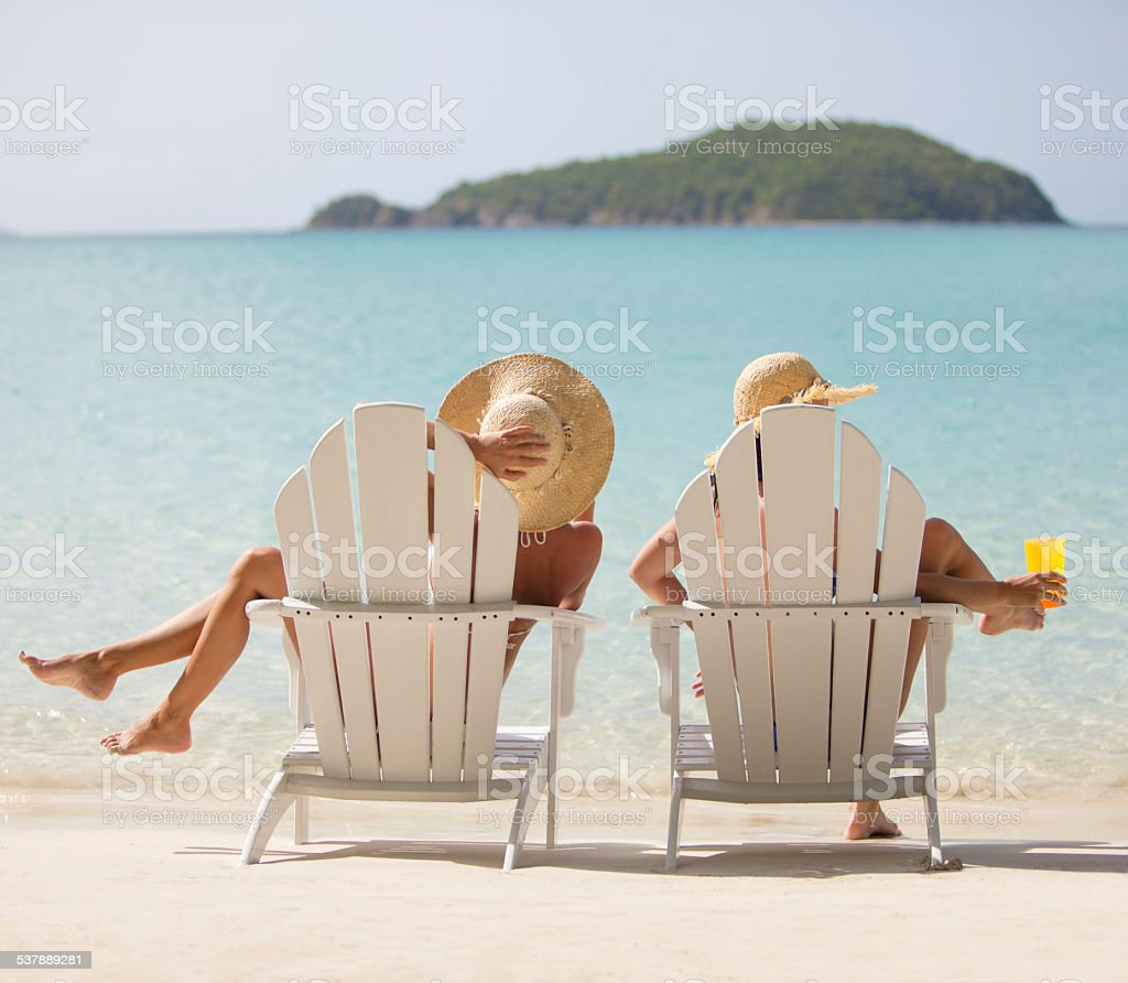 two unrecognizable women in beach chairs enjoying the Caribbean views stock photo