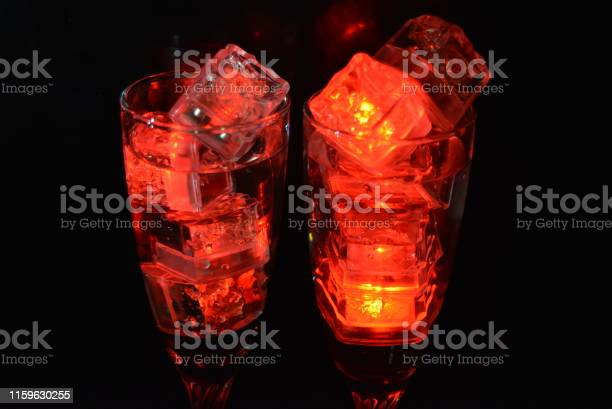 Photo of Two unusual glasses of champagne with a drink and bright red ice chips. Plastic ice cubes of ice illuminating the drink in each glass on a black background, an impressive photo and the feast of St. Valentine, the holiday of all lovers.
