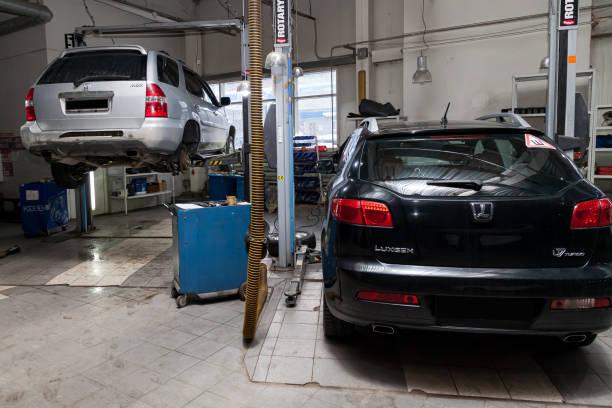 兩輛二手車Acura MDX和Luxgen在一輛電梯上舉車,用於修理汽車修理店的底盤和發動機。汽車服務業。圖像檔