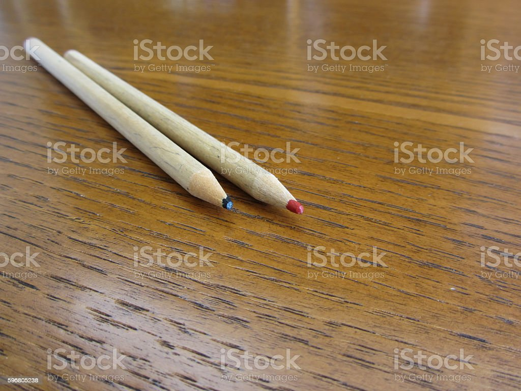 Two used colored pencils on wooden table stock photo