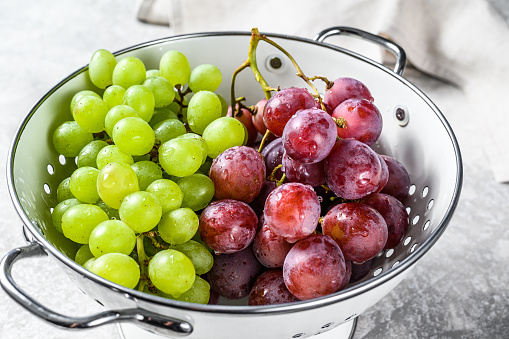 Two varieties of grapes, red and green in a colander. Gray background. Top view.