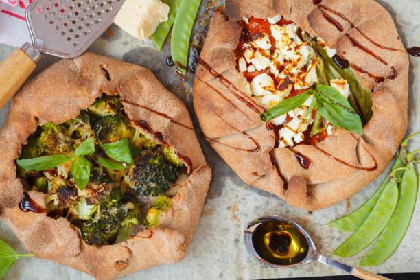 zwei vegetarische crostatas oder galette mit brokkoli, tomaten, käse und feta-käse auf ein backblech legen. - crostata stock-fotos und bilder