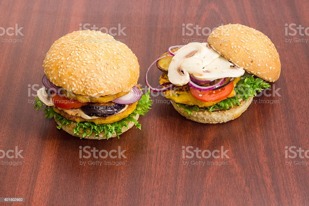 Two veggie burger with vegetables patties on a wooden surface Lizenzfreies stock-foto
