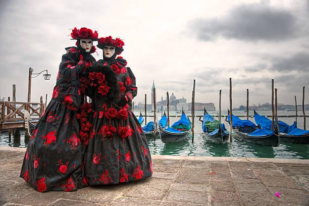 zwei venezianische masken in san marco square entfernt. venedig, italien. - rosa camo party stock-fotos und bilder