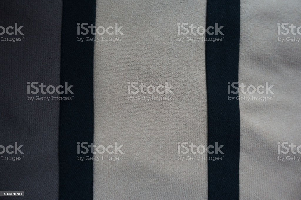 Two vertical black ribbons sewn to grey and beige fabric stock photo
