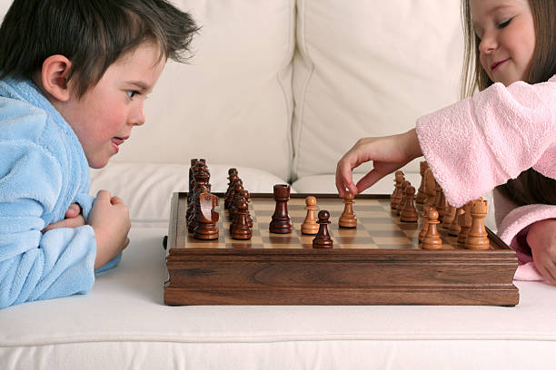Two very smart kids playing chess after just waking up stock photo