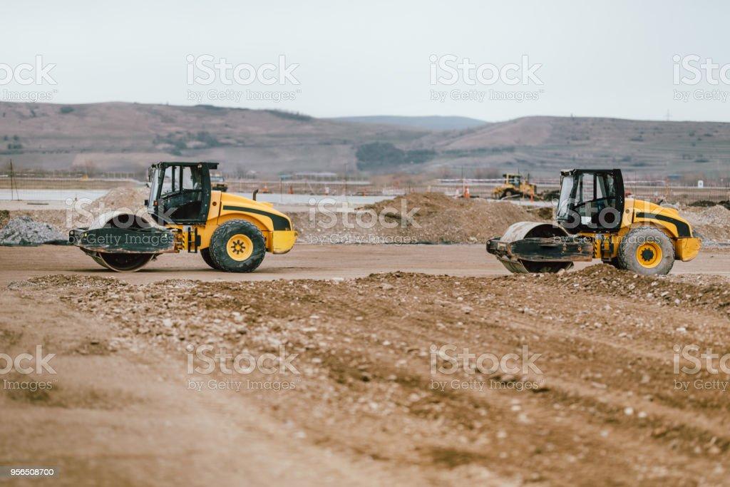 Zwei Boden-Walzenzüge im Straßenbau. Industrielle Baustellen mit schweren Maschinen in Baustelle - Lizenzfrei Aktivitäten und Sport Stock-Foto