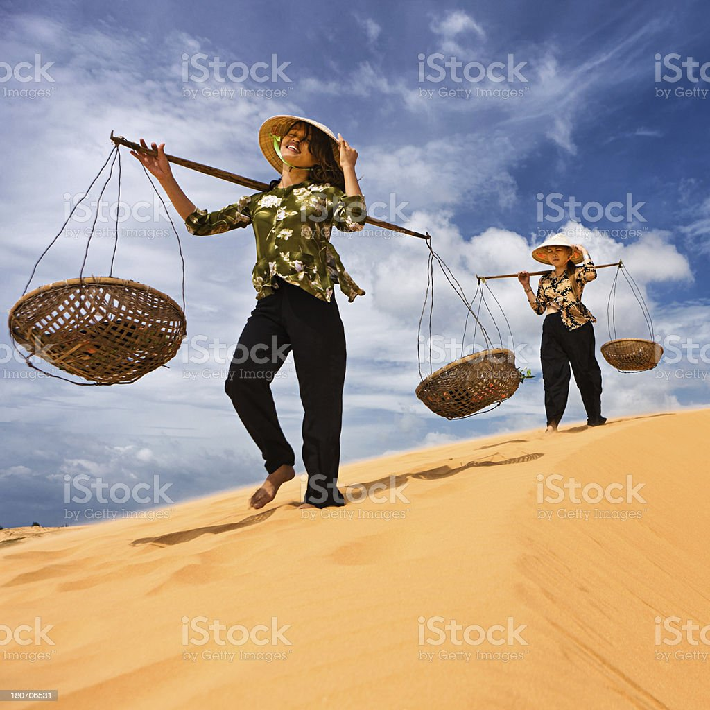 Two Vietnamese women crossing sand dunes royalty-free stock photo