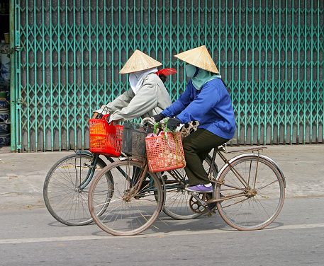 Two Vietnamese women wearing conical hats riding old bicycles