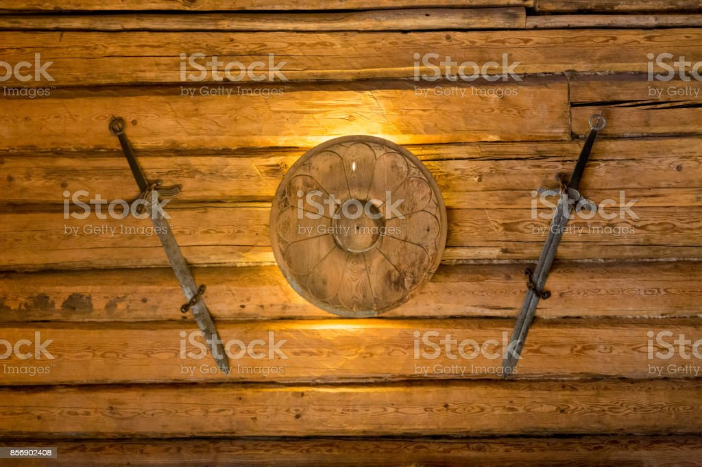 Two viking swords hanging on wall with shield stock photo