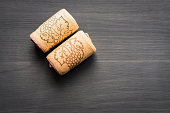 two vine corks on black wooden background with cope space